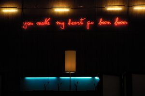 "Above the blue lit bar, a neon pink sign written by Fraco B reads ""you make my heart go boom boom"""