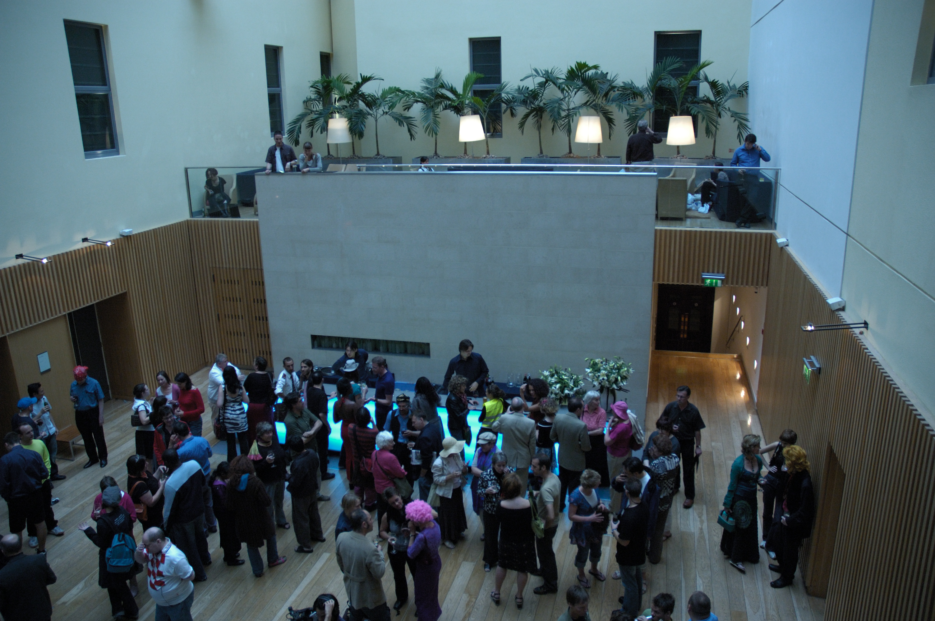 From above, a large group of people on the party floor, drinking near a blue lit bar.