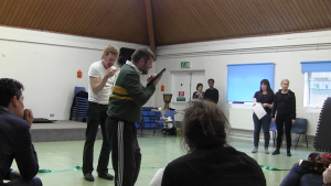 Two white male performers in a rehearsal room reading from their script with audience members watching from the foreground.