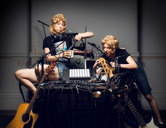 Two white women in blond curly hair pieces perch on a table full of cables entwined with musical instruments and microphones.