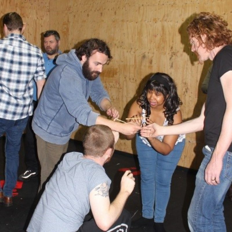 A tall white man with dark hair and a beard, a black woman with long curled hair, a white man with red curly hair and a white man with a buzz cut stand or crouch in a circle. Everyone is intently focusing on their hands, which hold chopsticks balanced on fingertips