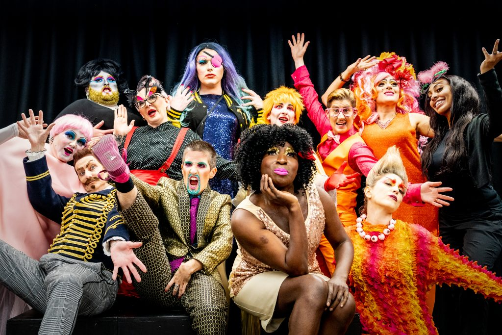 A celebratory group shot of visually impaired drag artists, all dressed in a variety of colourful and outlandish costumes. Some are posing while others grin and have their hands in the air.