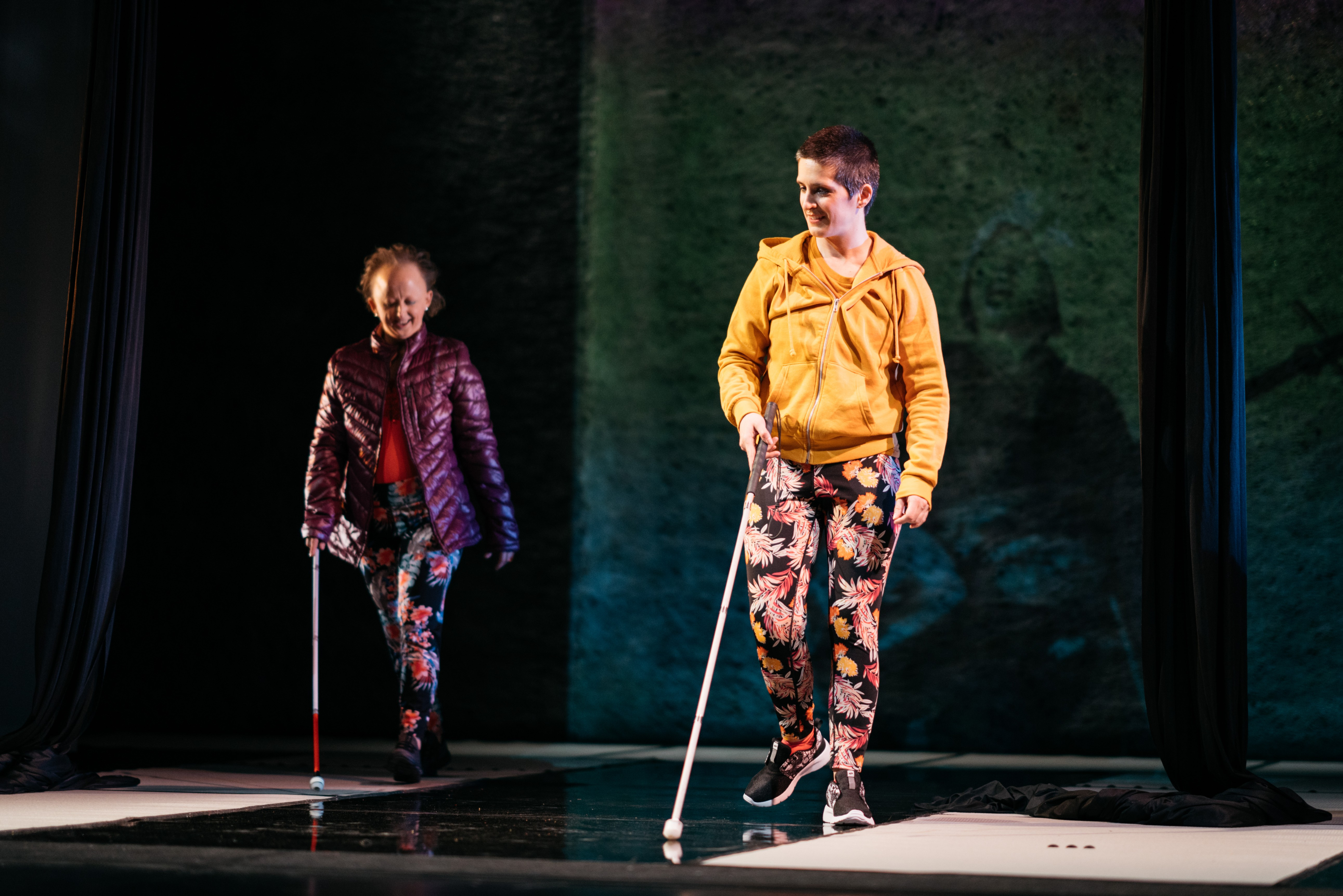 A full landscape shot of two white women walking onstage using white canes to guide them