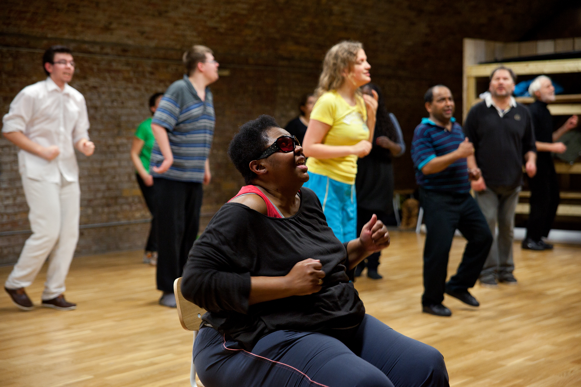 A visually impaired black woman wearing tinted glasses sits in a centre of a rehearsal room, arms in right angle motion. A group of visually impaired participants are dance behind her.