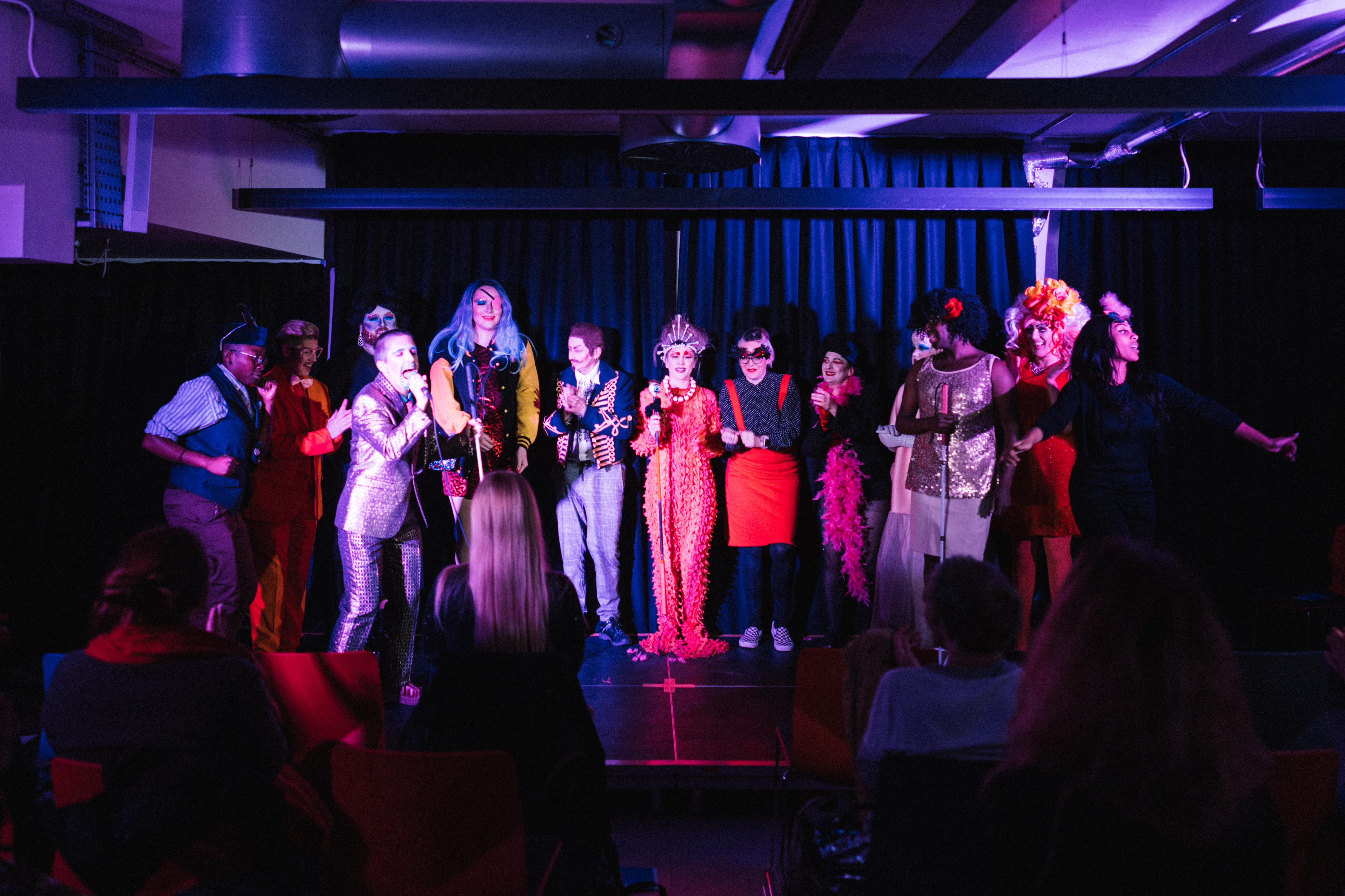 The drag performers standing side by side on the stage, some of them clapping. A white drag king stands on the left singing into the microphone
