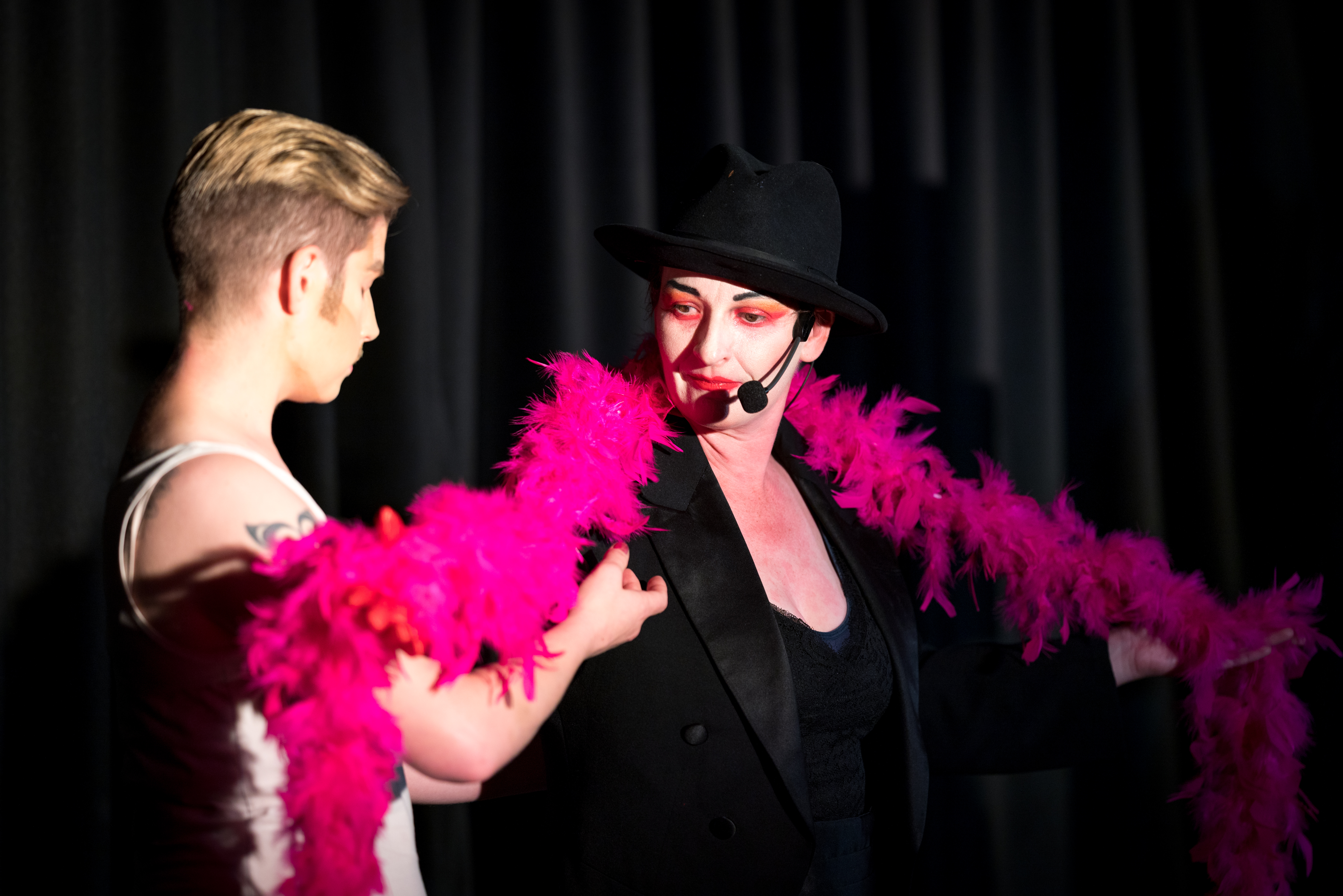 Two drag performers on stage. Right, a white woman with black bowler hat, a long pink feather boa and black suit jacket. The performer on the left is reaching up to the boa.