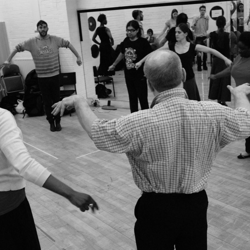 A group of participants in flamenco class standing in a large circle, their arms outstretched and curved in motion. A black and white image.