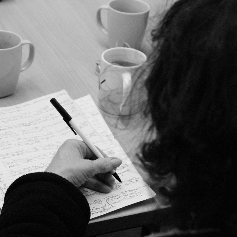 A close crop of someone writing in a notebook at a table, taken from the perspective of someone standing behind their shoulder.