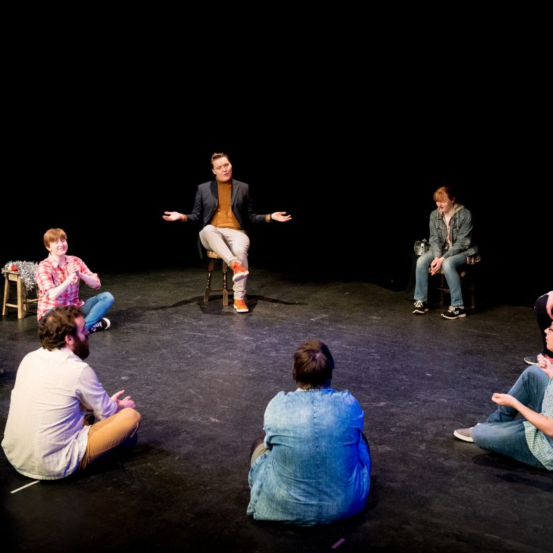 A group of eight workshop participants sitting in a circle on stage in a black box theatre. A man is sitting with legs crossed in the back with his hands in a 'what if' pose while the others sit crosslegged or on chairs with their attention to him