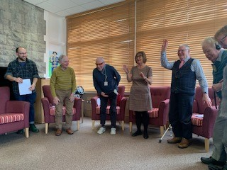 Six participants standing in a half semi circle midway through a storytelling session, an older man on the left has his hands up in dance, a woman next to him is clapping, everyone is smiling and cheery