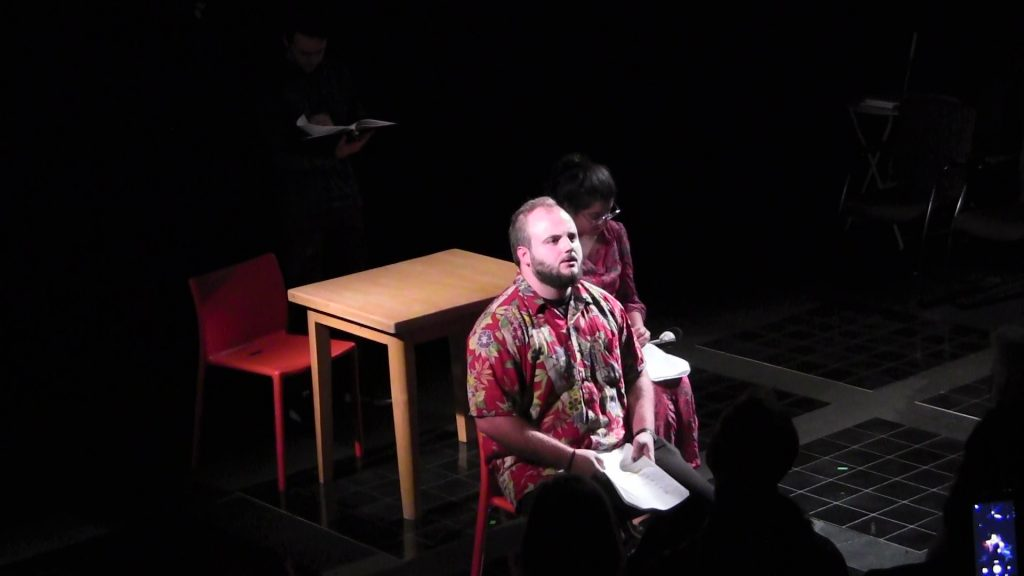 A young white man sitting in front of the stage, reading off his script. An Asian woman sitting at a table is in the background.