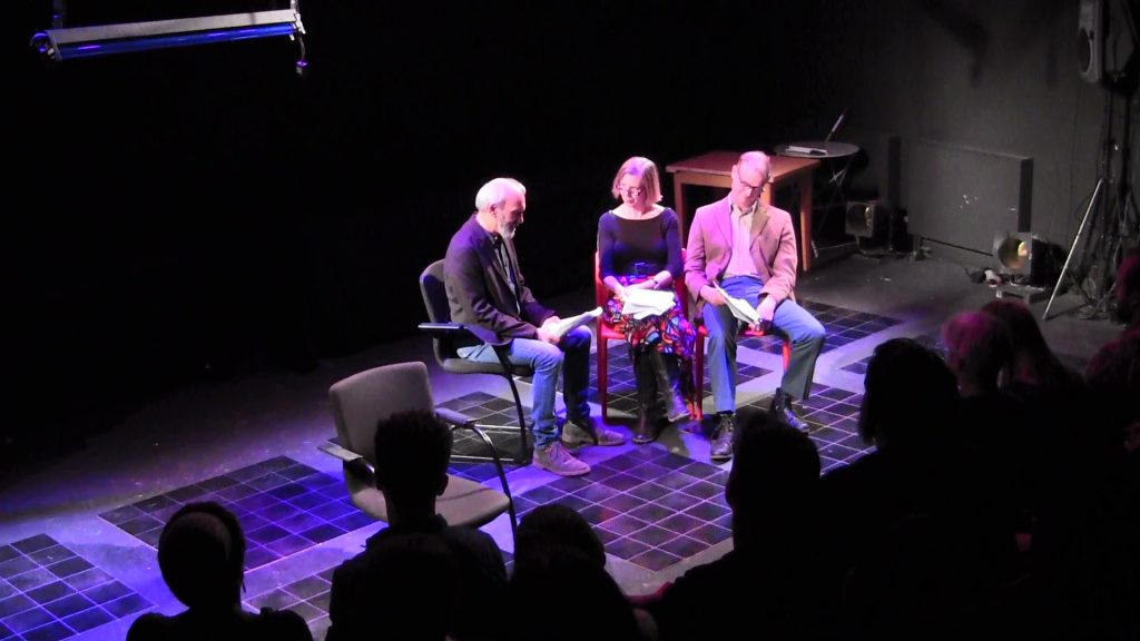 Three people sitting side by side on the stage, from left to right, an older white man is reading from a script, an older white woman listening to him speak, and an older white man looking at a script on his lap.