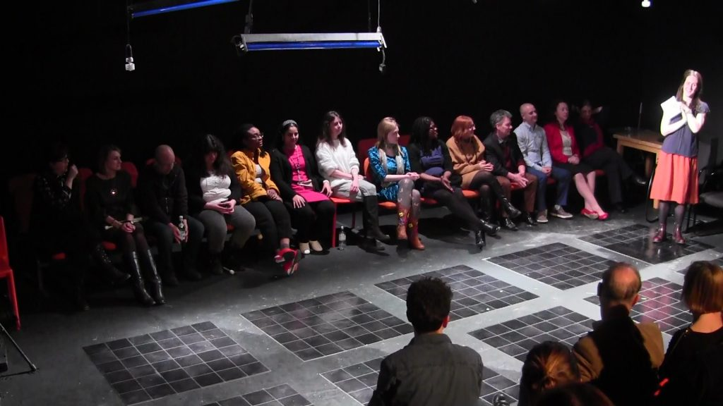 The participating writers sit in a row on stage, with the backs of the front row of the audience in the foreground. A white woman on the right is facing the audience, receiving questions for a Q&A
