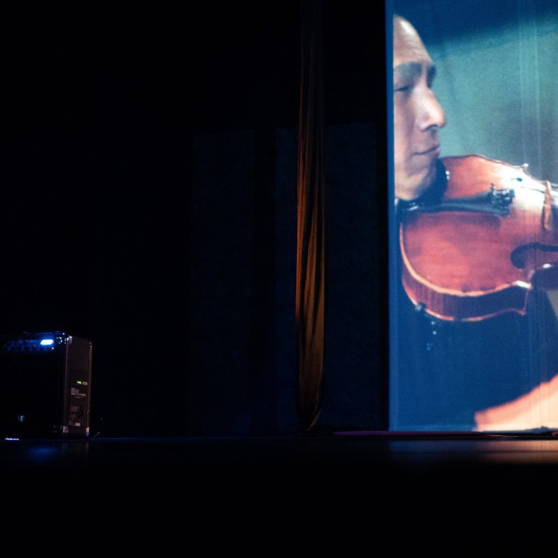 A white woman sits downstage right watching a 14 ft projection of an East Asian man playing the viola
