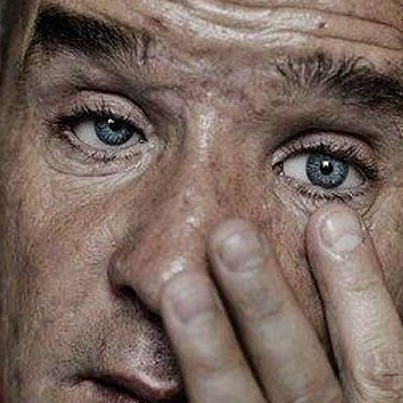 A close up of a middle aged white man's face. His expression is haggard and his fingers touch his left cheek right below his eye.
