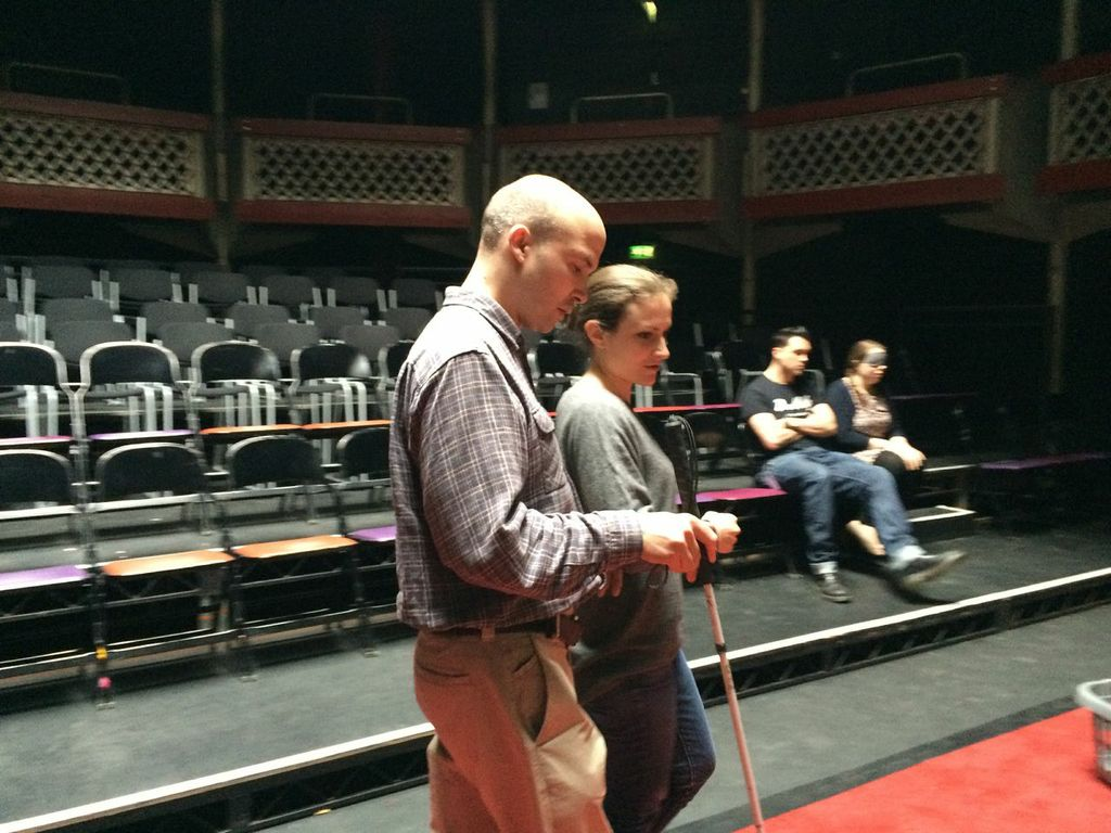 A white woman guiding a visually impaired white man on an auditorium stage