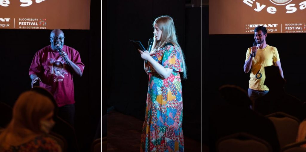 From left to right: A vertical shot of Maverick, a man of African or Caribbean heritage talking into the microphone and grinning; A vertical close up of Amy, a young white woman, from a side perspective. She is spotlighted by stage lights and reading off her iPad with a microphone; A vertical shot of Naqi, a man of South Asian heritage smiling while talking into the microphone