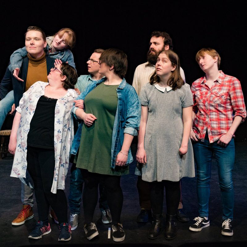 A group of visually impaired and blind actors standing on stage, their attention directed to one of them being piggybacked.