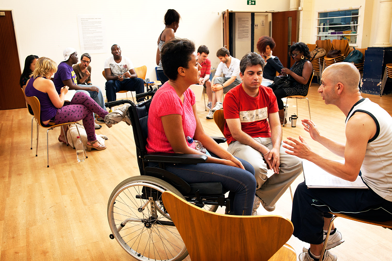 A workshop setting: small groups of people sit on chairs in circles talking amongst themselves.