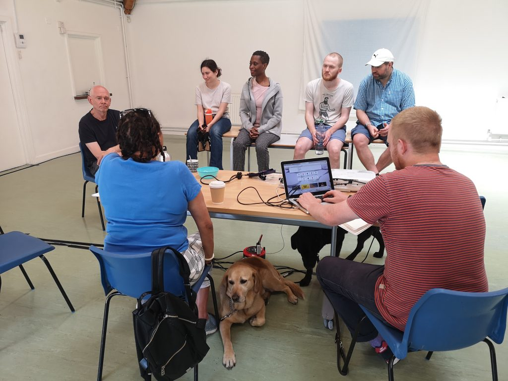 Five actors and the stage manager sit and listen while the director feeds back. A guide dog lays at the director's feet.