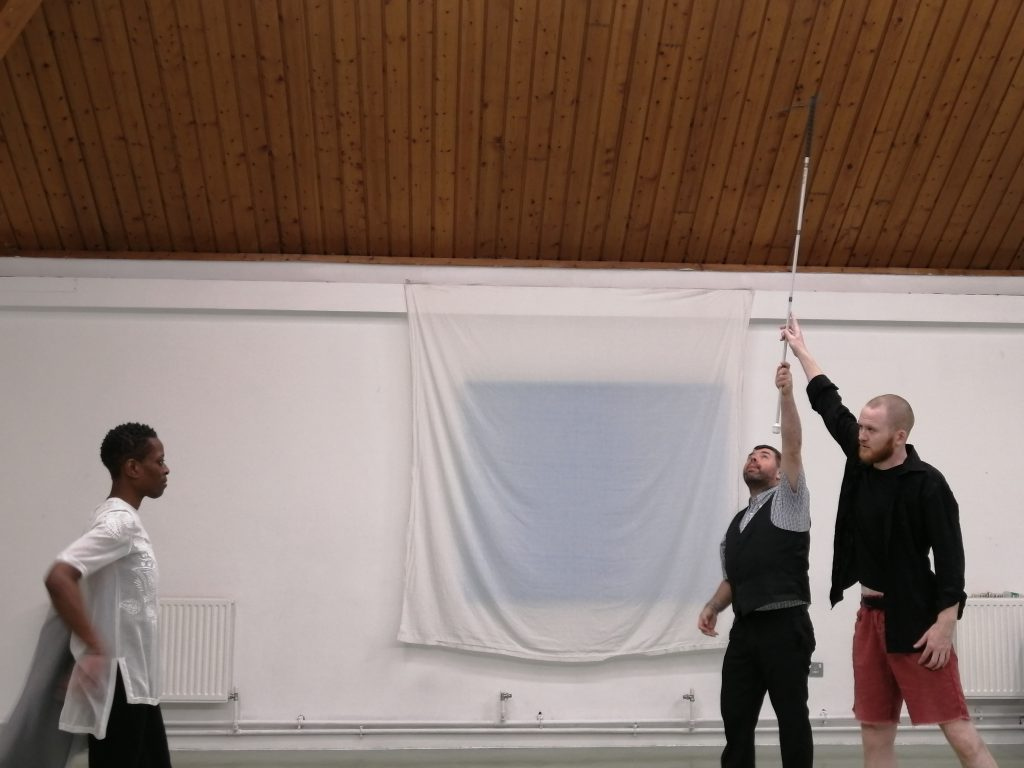 Two white men grasp a cane held high above their heads while a Black woman looks on